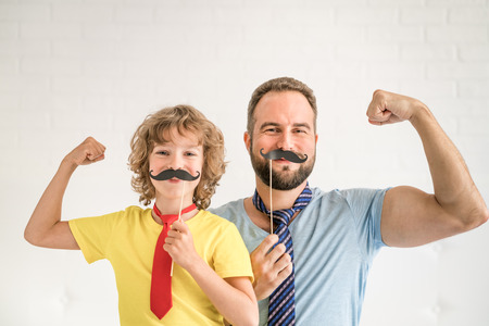 Foto de Funny man and kid with fake mustache. Happy family playing in home - Imagen libre de derechos