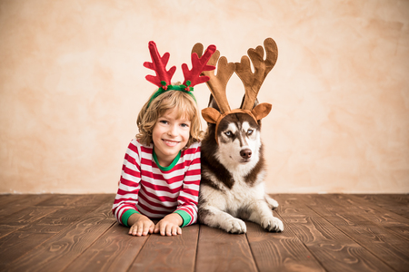 Photo for Happy child and dog on Christmas eve. Kid and pet dressed in Santa Claus hat. Girl having fun with husky at home. Chinese calendar new year concept - Royalty Free Image