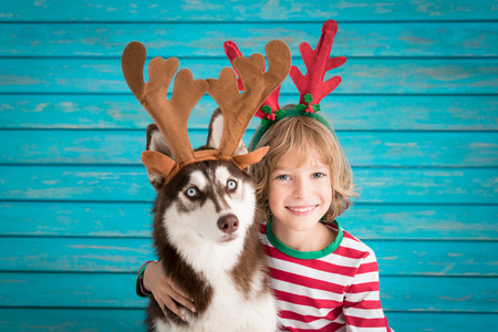Foto de Happy child and dog on Christmas eve. Kid and pet dressed in Santa Claus hat. Girl having fun with husky at home. Chinese calendar new year concept - Imagen libre de derechos