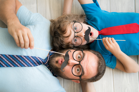 Photo pour Funny man and kid with fake mustache. Happy family playing in home - image libre de droit