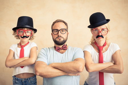 Photo pour Funny man, woman and kid with fake mustache. Happy family playing in home - image libre de droit
