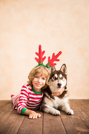 Photo pour Happy child and dog on Christmas eve. Kid and pet dressed in Santa Claus hat. Girl having fun with husky at home. Chinese calendar new year concept - image libre de droit