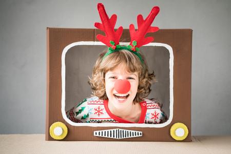 Foto de Happy child playing at home. Funny kid on Christmas eve. Xmas winter holiday concept - Imagen libre de derechos