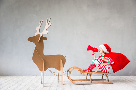 Foto de Happy child riding Christmas sleigh. Kid having fun at home. Xmas holiday concept - Imagen libre de derechos
