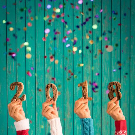 Photo pour Happy New Year 2018! Confetti falling against wooden background - image libre de droit