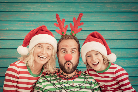 Foto de Happy family playing at home. Funny father; mother and child on Christmas eve. Xmas winter holiday concept - Imagen libre de derechos