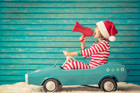 Foto de Happy child playing at home. Funny kid on Christmas eve. Xmas winter holiday concept - Imagen libre de derechos