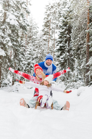 Foto de Happy family having fun outdoor. Child, mother and father playing in winter time. Active healthy lifestyle concept - Imagen libre de derechos