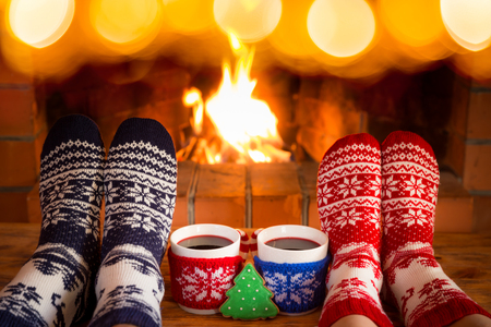 Photo pour Couple in Christmas socks near fireplace. Friends having fun together. People relaxing at home. Winter holiday Xmas and New Year concept - image libre de droit