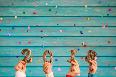 Foto de Happy New Year 2018! Confetti falling against wooden background - Imagen libre de derechos