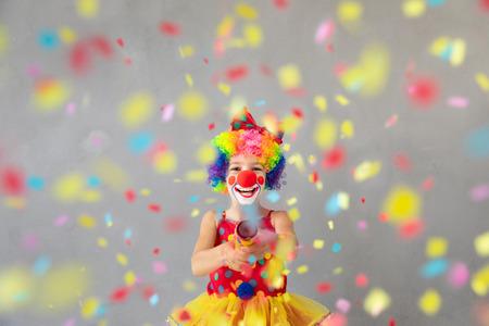 Foto de Funny kid clown with party poppers. Happy child playing at home. 1 April Fool's day concept - Imagen libre de derechos
