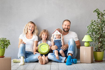 Foto de Happy family with two kids playing into new home. Father, mother and children having fun together. Moving house day and real estate concept - Imagen libre de derechos