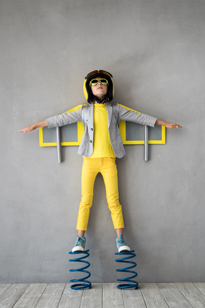 Photo pour Happy child playing with toy jetpack. Kid pilot standing on spring. Success, innovation and leader concept - image libre de droit
