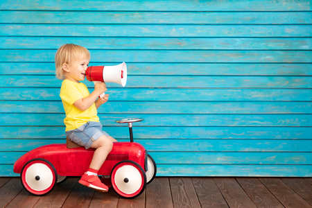 Photo pour Funny child riding bike. Happy kid having fun at home. Spring family holiday concept. Mother's day - image libre de droit