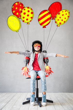 Photo pour Happy child playing with toy jetpack. Kid pilot ready to fly. Success, innovation and leader concept - image libre de droit