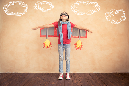 Photo pour Happy child playing with toy jet pack. Kid pilot ready to fly. Success, innovation and leader concept - image libre de droit