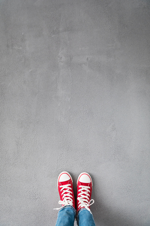 Photo pour Feet in red sneakers on concrete background - image libre de droit