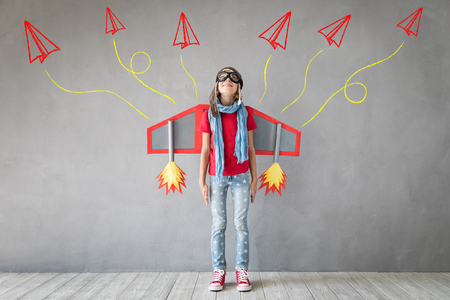 Photo pour Happy child playing with toy jetpack. Kid pilot having fun at home. Success, innovation and leader concept - image libre de droit