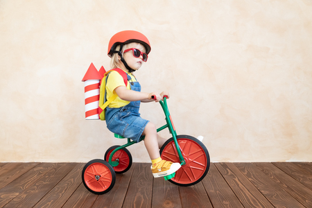 Photo pour Kid with toy paper rocket. Child playing at home. Success, imagination and innovation technology concept - image libre de droit