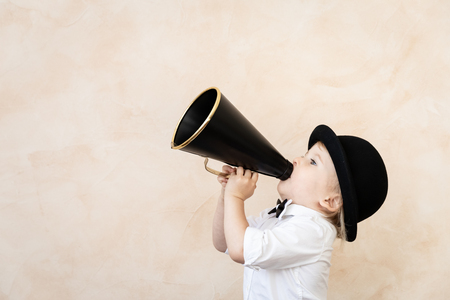 Photo for Funny child playing at home. Kid shouting through vintage megaphone. Communication and retro cinema concept - Royalty Free Image