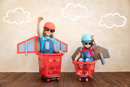 Photo pour Kids with jet pack racing on shopping cart. Children playing at home. Success, imagination and innovation technology concept - image libre de droit