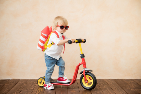 Photo pour Happy child playing with toy rocket at home. Funny kid driving scooter. Success and win concept - image libre de droit