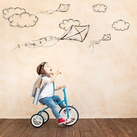 Photo pour Funny kid with toy jet pack. Happy child playing at home. Success, imagination and innovation technology concept - image libre de droit