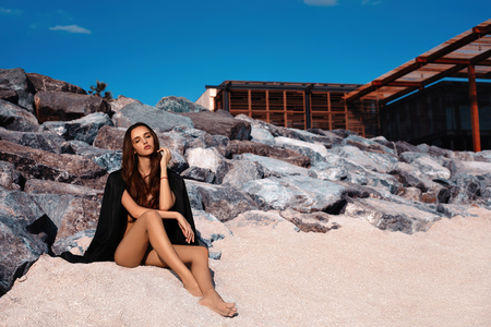 Photo for Pretty girl with perfect body sitting on sand behind the rocks at the spa resort - Royalty Free Image