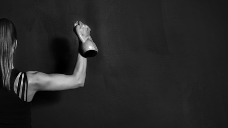 Foto de Fitness Athletic Strong Woman Workout with Dumbbell showing biceps on black background - Imagen libre de derechos