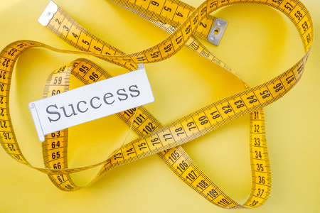 Photo pour yellow measuring tap ,diet, dream to be slim, healthy concept, results of fitness jogging and sticking to healthy lifestyle.success. measuring tape and word success - conceptual.dream of a beautiful figure - image libre de droit