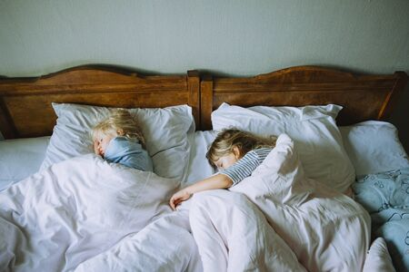 Foto de Two little girls sleeping in a big rustic bed with white linen - Imagen libre de derechos