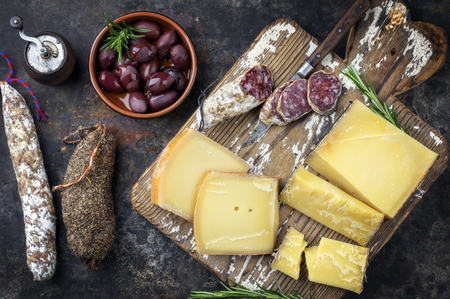 Foto de Traditional French cold cuts with cheese and salami as top view on old cutting board - Imagen libre de derechos