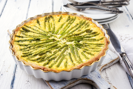 Photo pour Tart with green asparagus on backing form as top view on wooden table - image libre de droit