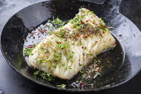 Photo pour Fried cod fish fillet with spice and cress as close-up in a cast iron pan - image libre de droit