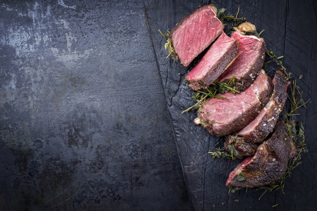 Photo pour Barbecue dry aged Kobe rib eye steak as close-up on a burnt board with copy space left  - image libre de droit