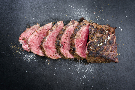 Foto de Barbecue dry aged caveman wagyu chateaubriand steak sliced as close-up on a board  - Imagen libre de derechos