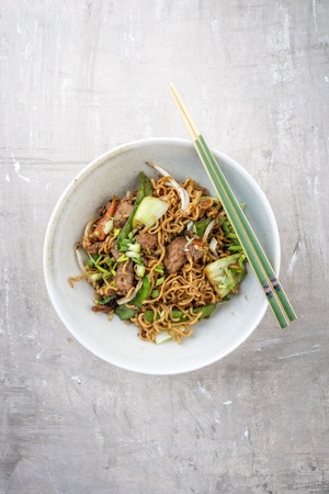 Photo pour Traditional stir-fried Thai phat mama mie noodles with pork and vegetables as top view in a bowl with copy space - image libre de droit