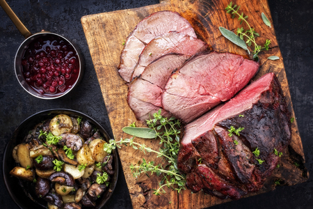 Photo for Barbecue dry aged haunch of venison with mushroom and potatoes as close-up on an old cutting board - Royalty Free Image