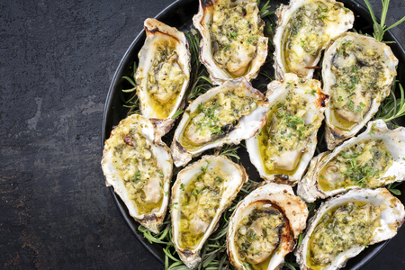 Foto de Barbecue overbaked fresh opened oyster with garlic and herbs offered as top view on a tray with copy space left - Imagen libre de derechos