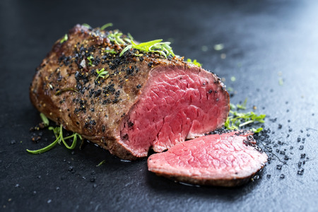 Photo for Traditional barbecue dry aged wagyu beef fillet steak with herb and spice marinated as closeup on a black board - Royalty Free Image