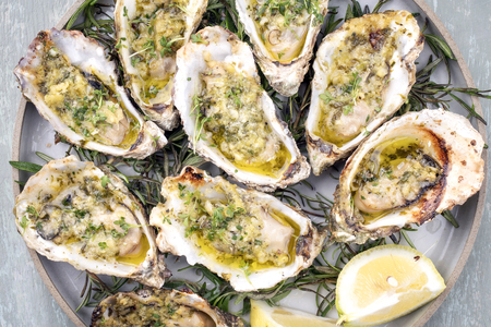 Photo pour Barbecue overbaked fresh opened oyster with garlic, lemon and herbs offered as top view on a plate - image libre de droit
