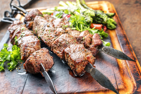 Photo pour Traditional Russian shashlik on a barbecue skewer with green asparagus and paprika as close up on a burnt cutting board - image libre de droit