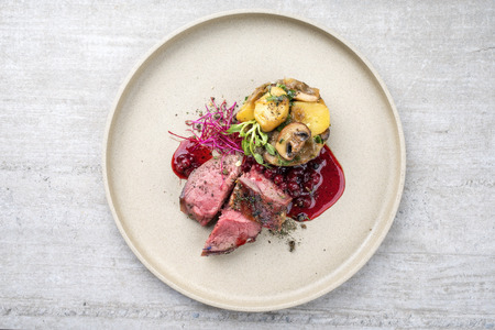 Foto de Traditional barbecue dry aged sliced venison fillet steak with potato mushroom terrine and cowberry sauce as top view on a plate with copy space - Imagen libre de derechos