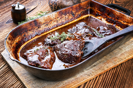 Photo pour Traditional German braised veal cheeks in brown sauce with mushroom and onions as closeup in a stewpot - image libre de droit