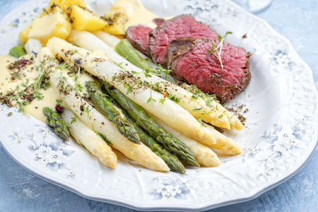 Photo pour Traditional white and green asparagus with barbecue dry aged sliced beef fillet and fried potatoes served as closeup on a shabby chic design plate - image libre de droit