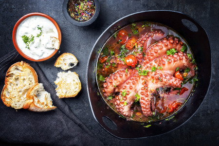 Photo pour Traditional Greek octopus braised cooked with tomatoes and herbs in ouzo sauce with tzatziki as top view in a cast-iron saucepan - image libre de droit