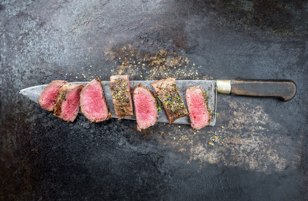Photo pour Traditional barbecue aged venison backstrap roast sliced with herbs as top view on a large knife with rustic background with copy space - image libre de droit