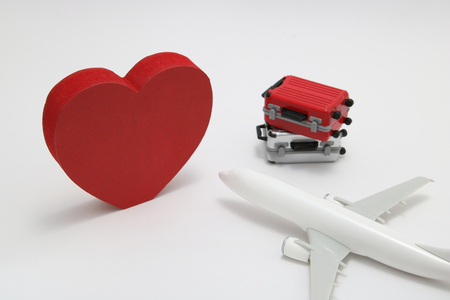Photo pour Miniature two suitcases, airplane toy, and a red heart on white background. Concept of honeymoon by airplane. - image libre de droit