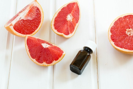 Photo for Essential oil in glass bottle with fresh, juicy grapefruit. Spa concept.  Selective focus. - Royalty Free Image