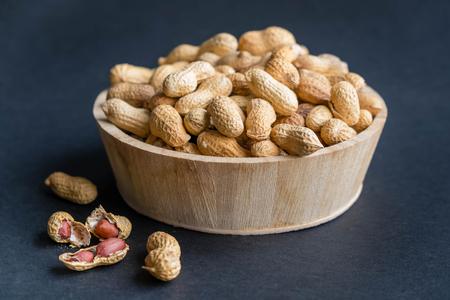 Photo pour Raw peanuts in bowl on a black wooden table. - image libre de droit